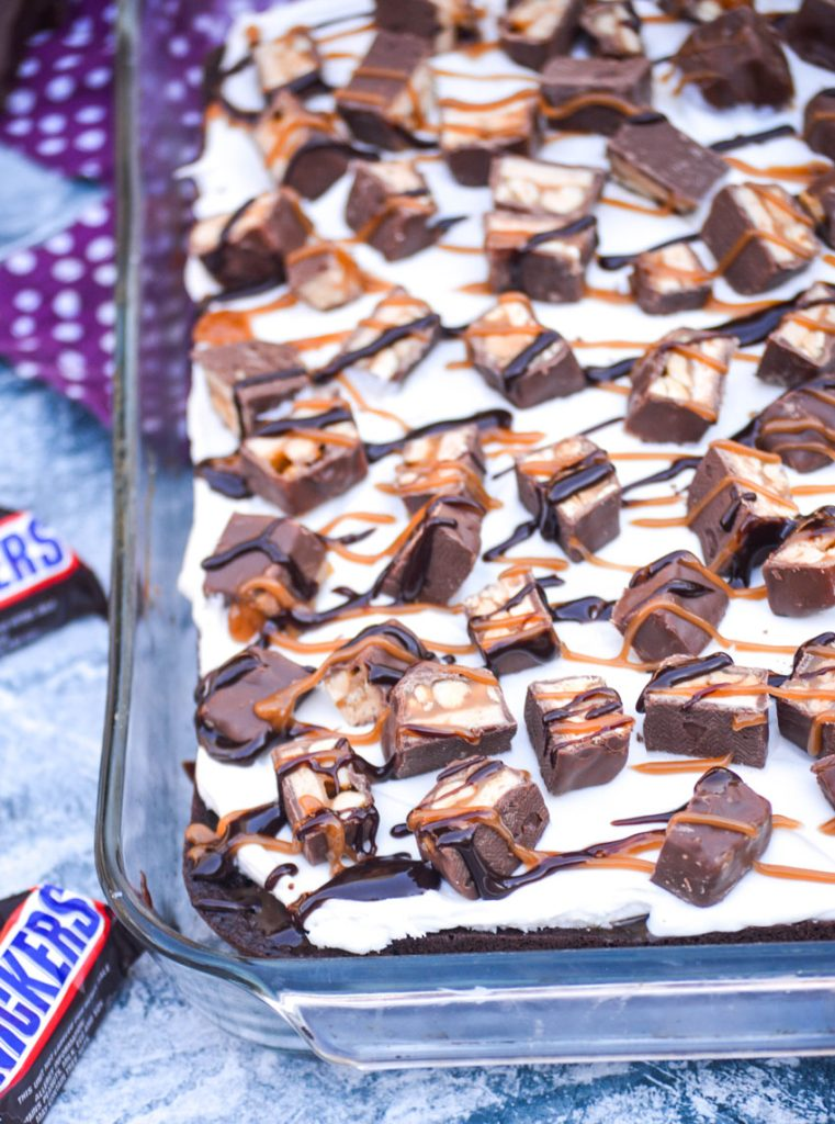 "snickers poke cake made in a glass 9x13"" baking dish with fun size snickers bars in the background"