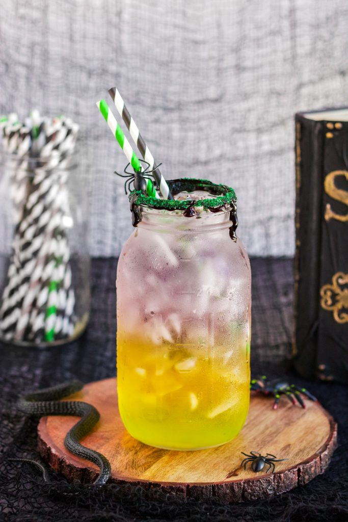 green, orange, and purple Halloween themed layered drink with ice in a glass mason jar rimmed with black icing and edible glitter