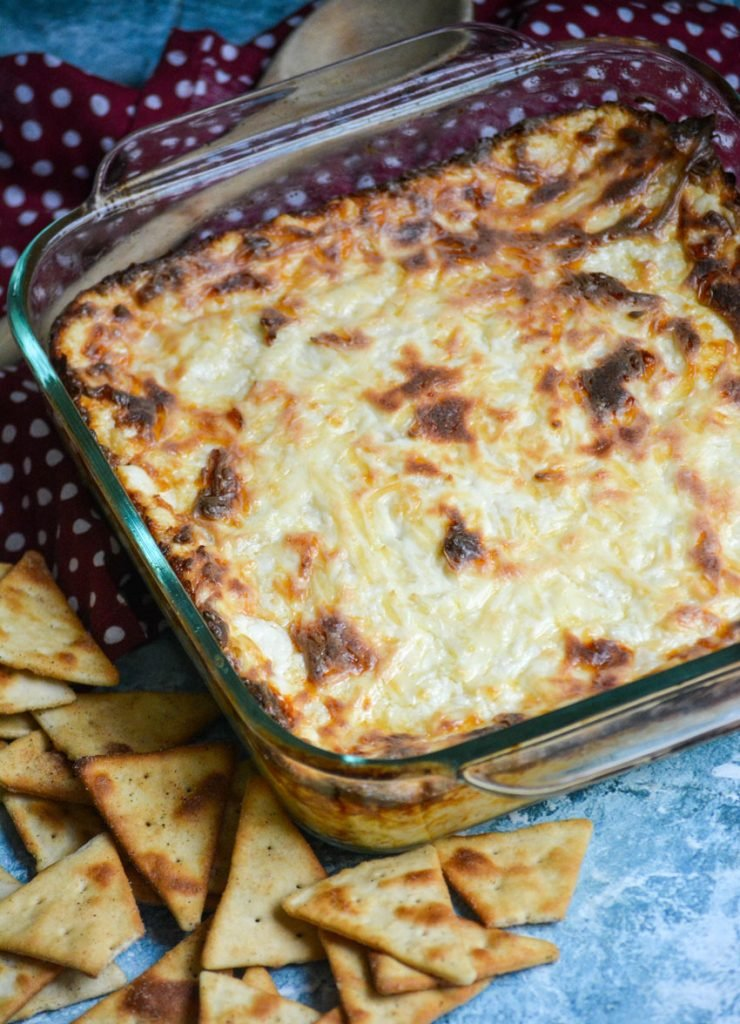 hot onion dip baked until a golden brown crust has formed on top in a glass square baking dish with pita chips on the side