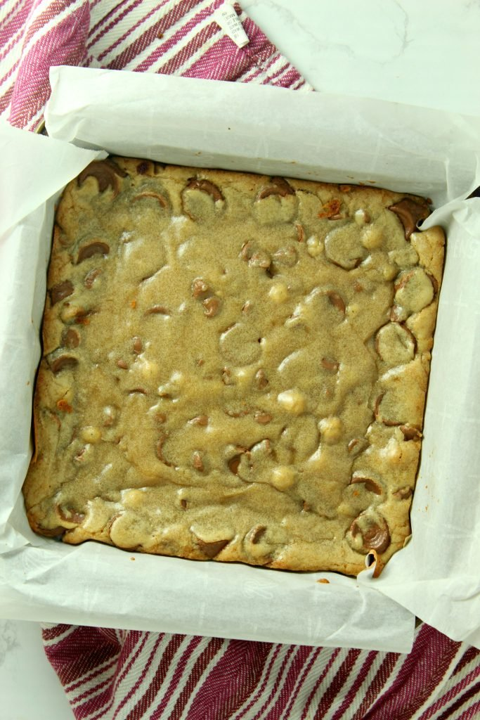 baked rolo chocolate chip blondies shown in a parchment paper lined baking dish