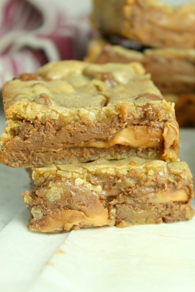 two chocolate chip caramel blondies stacked together to show the fudgey caramel studded insides