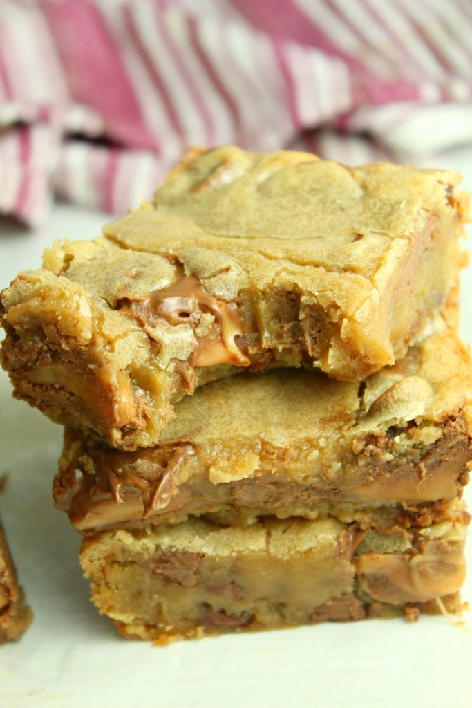 rolo chocolate chip blondie bars stacked three high with a bite clearly taken out of the top square showing the gooey caramel inside