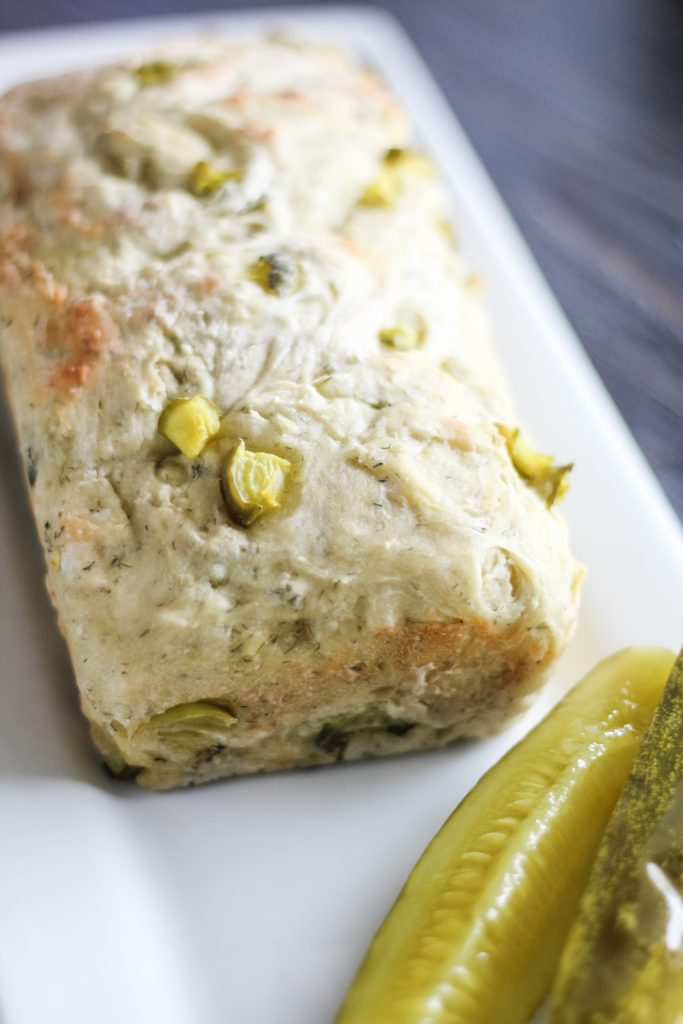 a loaf of dill pickle shown on a white serving platter