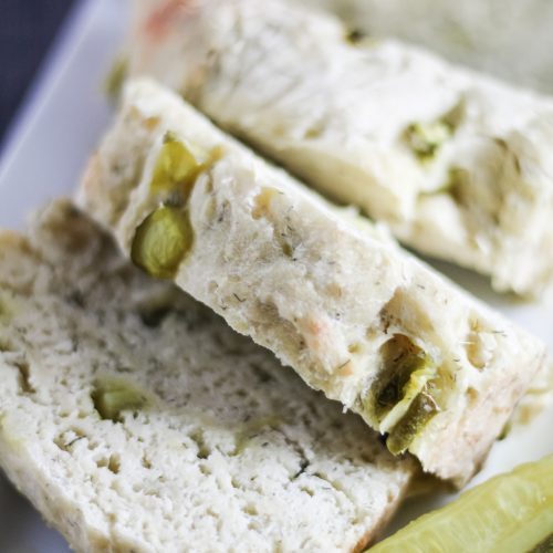 dill pickle bread shown sliced on a white serving platter with pickle spears on the side