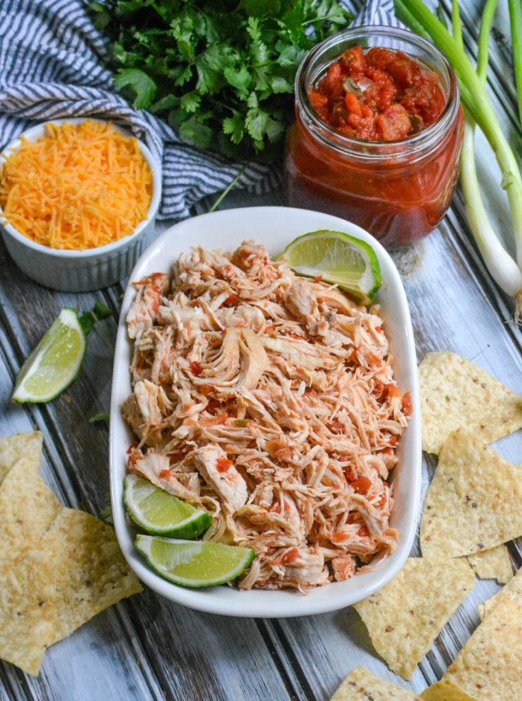 instant pot salsa chicken is shown shredded in a white corningware dish with fresh lime wedges and surrounded by tortilla chips, herbs, cheese, and salsa