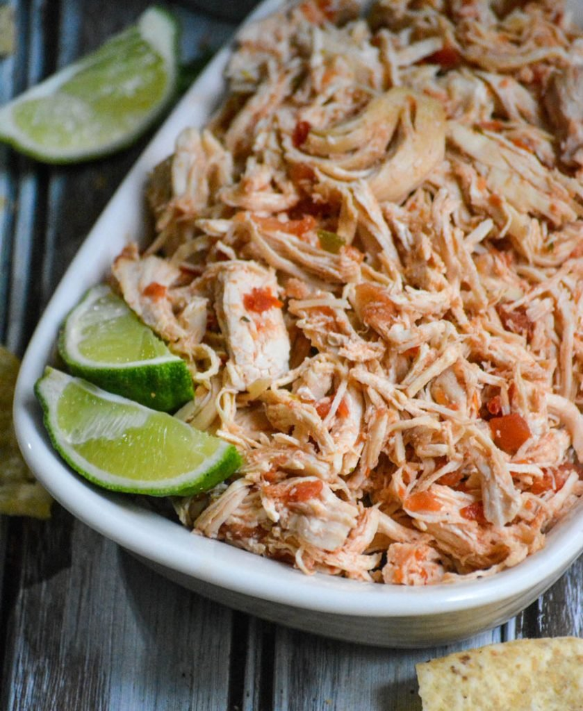 instant pot salsa chicken is shown shredded in a white corningware dish with fresh lime wedges