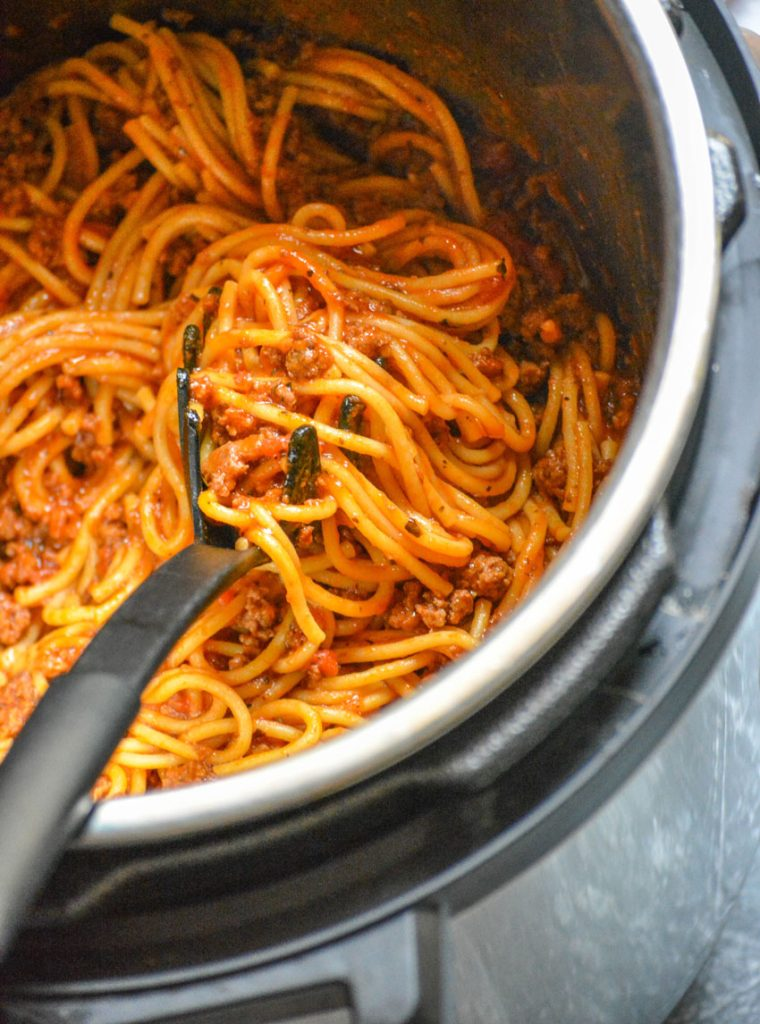 sauced cooked spaghetti being scooped out of the inner pot of pressure cooker with a black spaghetti fork