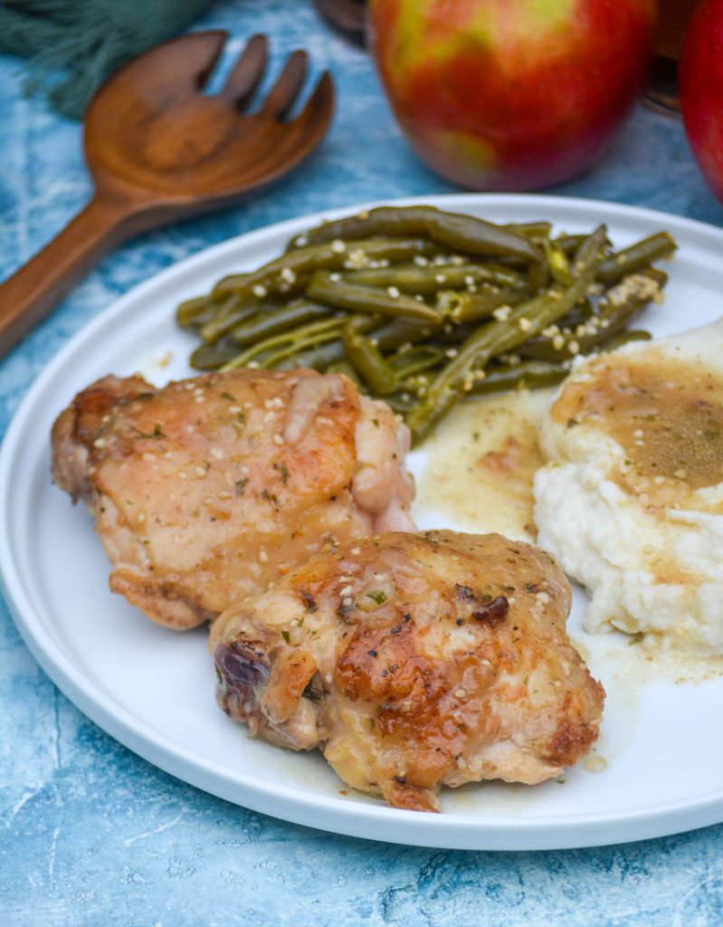 pan fried chicken thighs served on a white plate with apple cider gravy over mashed potatoes and green beans on the side