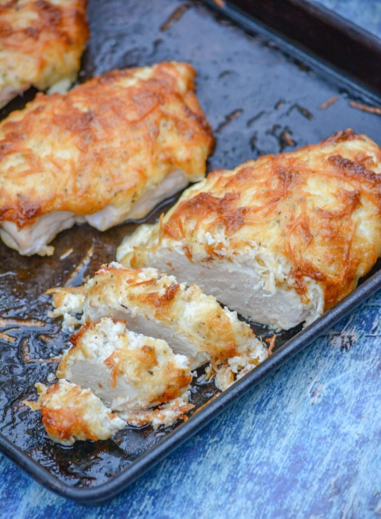 mayo parmesan crusted chicken shown sliced on a baking sheet