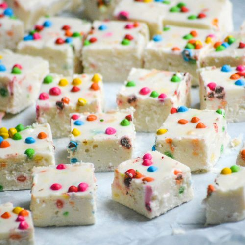 rainbow chip fudge shown cut into squares and laid out on parchment paper