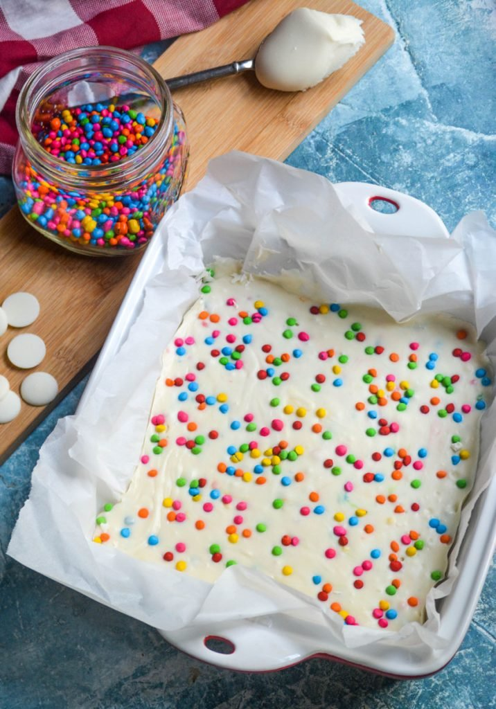 rainbow chip frosting shown in a parchment lined square baking dish