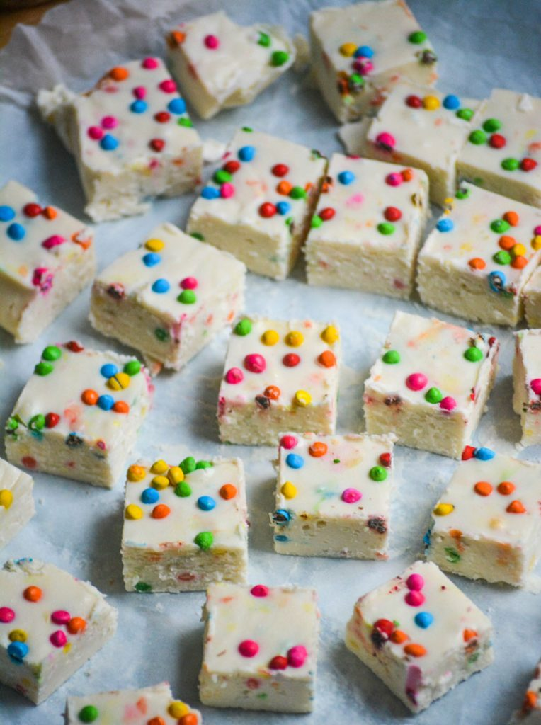 squares of rainbow chip frosting fudge spread out on a piece of crinkled parchment paper