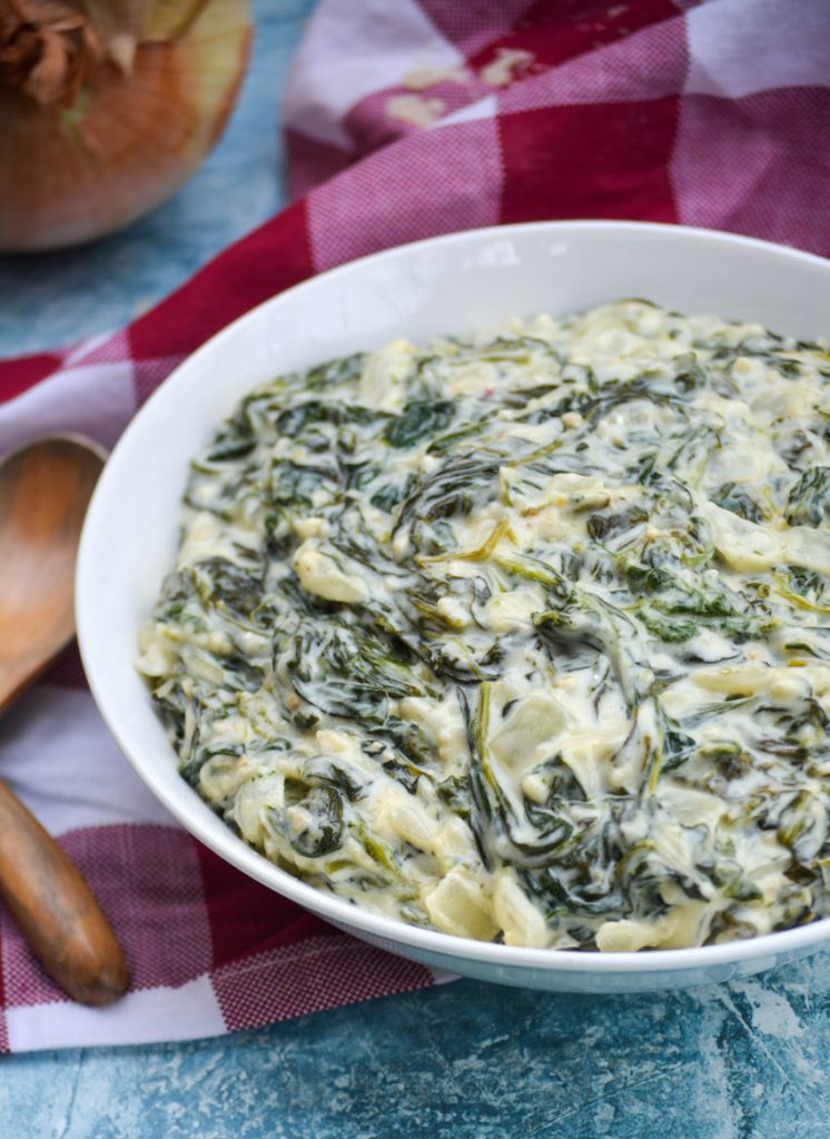 creamed spinach served in a shallow white bowl on a checkered cloth napkin with wooden spoons off to the side