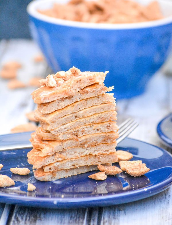 a cut out wedge of a stack of cinnamon toast crunch flavored pancakes served on a blue plate with cereal pieces on and around it
