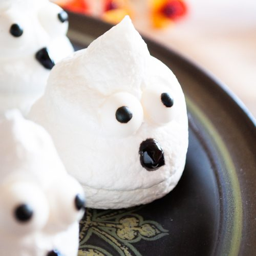 Boo Egg White Meringue Cookies sit on a black platter with Fall colored decor in the background
