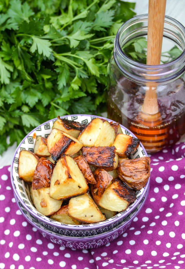 honey roasted red potatoes shown in a purple bowl with fresh herbs and a jar of honey in the background
