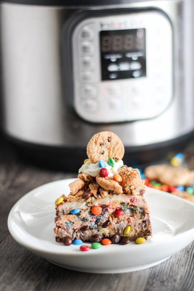 a sliced of instant pot monster cheesecake shown on a white plate topped with cookie chunks and mini m&ms shown in front of an instant pot pressure cookier