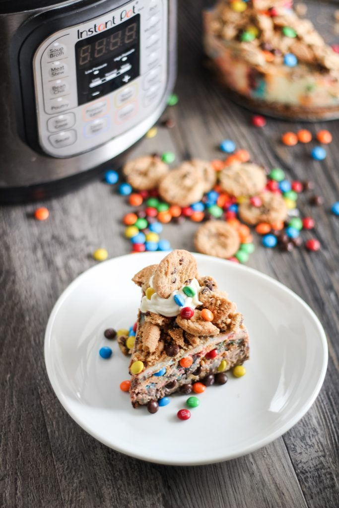 a sliced of instant pot monster cheesecake shown on a white plate topped with cookie chunks and mini m&ms