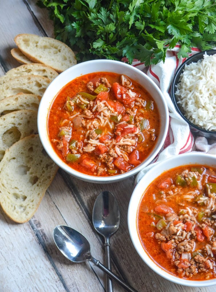 stuffed pepper soup made in the Instant Pot shown served in white bowls with sliced bread, spoons, and fresh herbs in the background