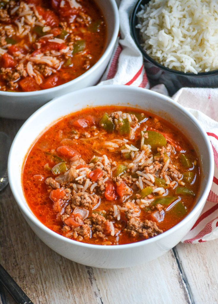 Instant Pot stuffed pepper soup shown in two white bowls on a wooden table top with a bowl of rice and striped cloth napkin in the background