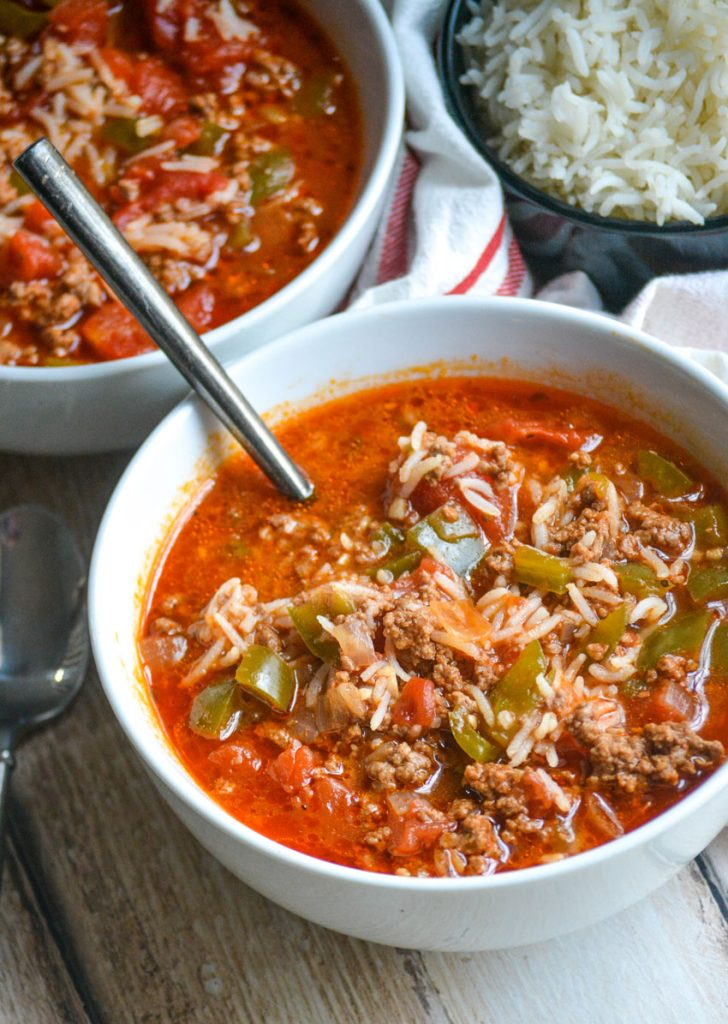 Instant Pot stuffed pepper soup shown in two white bowls on a wooden table top with a bowl of rice and striped cloth napkin in the background; a spoon is shown in one of the bowls