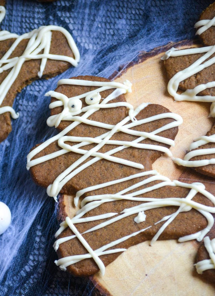 Halloween themed mummy gingerbread cookies on a wooden cutting board with spider webs in the background