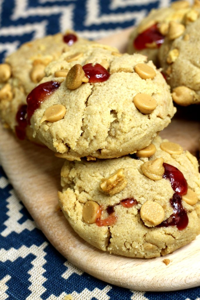 peanut butter jelly cookies stuffed with strawberry jam are piled on a wooden cutting board