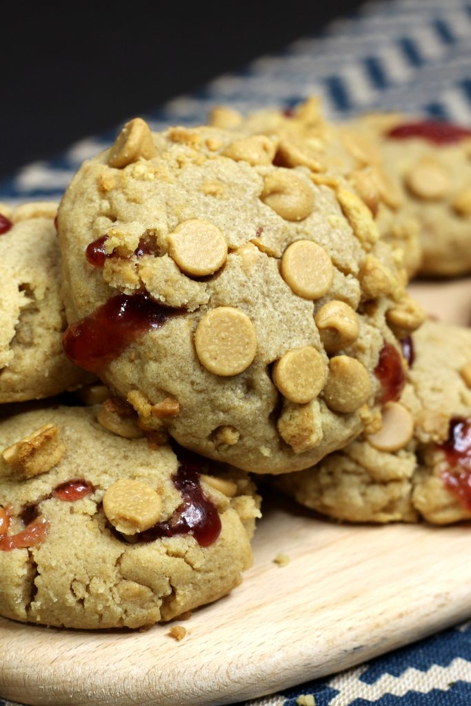 peanut butter jelly cookies piled on a wooden cutting board