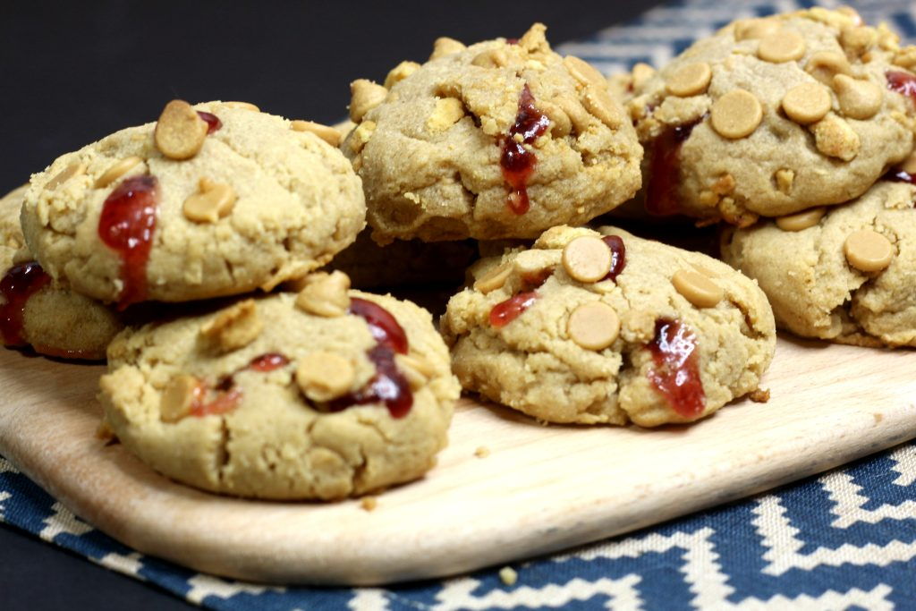 peanut butter and stuffed jelly cookies piled on a wooden cutting board