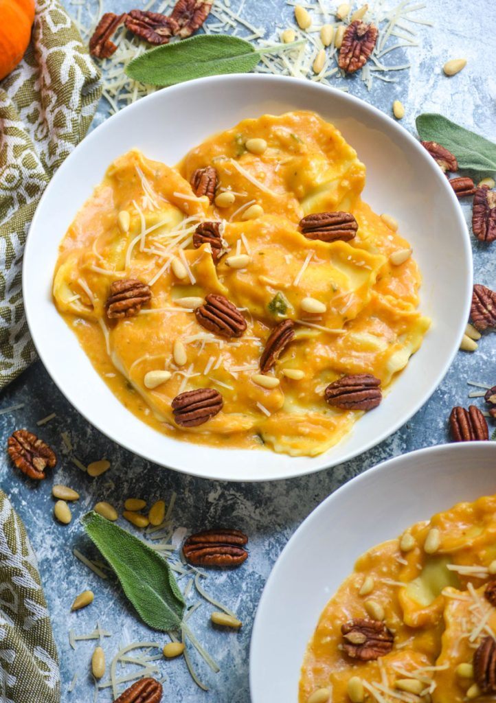 pumpkin alfredo sauce tossed with ravioli served in two white bowls with sage leaves and pecans in the background