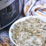 slow cooker green bean casserole served in a white bowl with a crockpot in the background