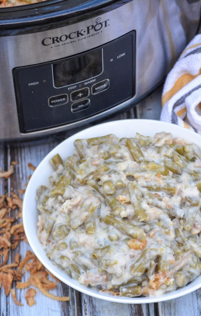 slow cooker green bean casserole shown in a white bowl with a crockpot in the background