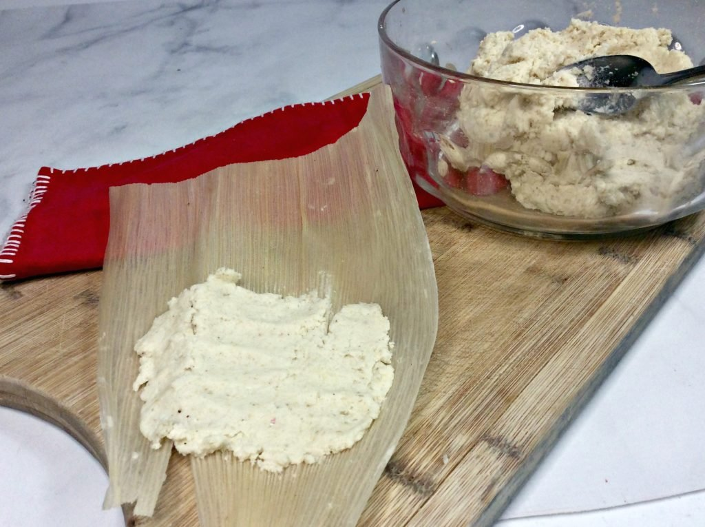 masa meal mix shown being spread on soft corn husk for instant pot tamales