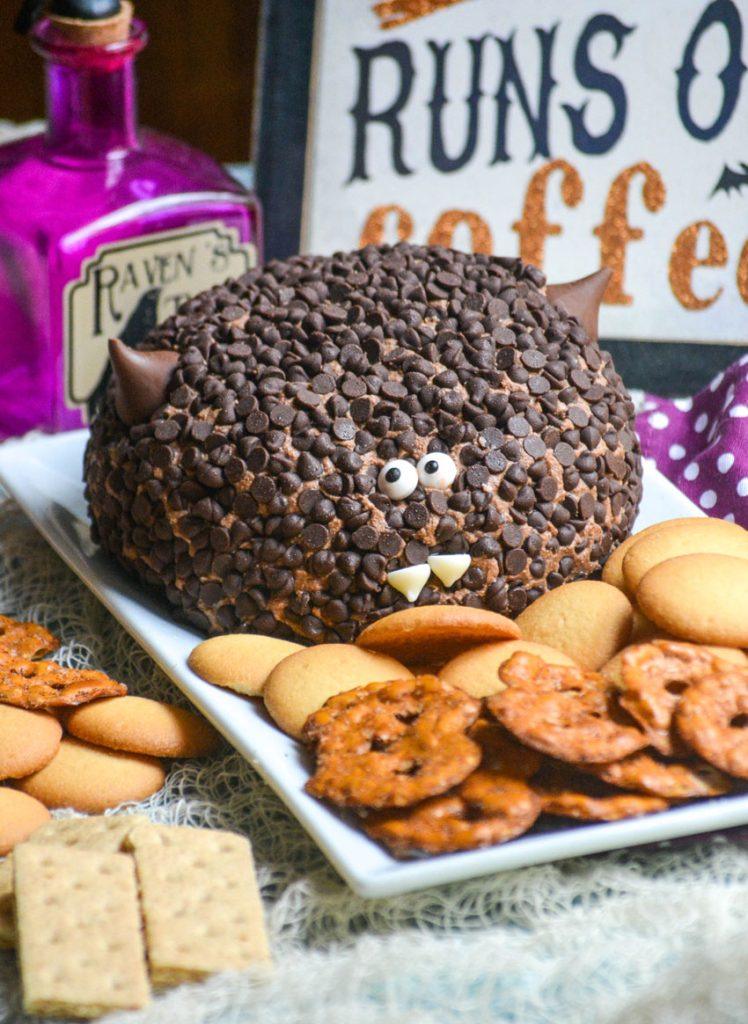 a triple chocolate dessert cheese ball covered in mini chocolate chips and made to look like a bat served on a white platter with pretzel chips and cookies for dipping