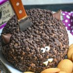 a triple chocolate dessert cheese ball covered in mini chocolate chips and made to look like a bat with a wooden handled spread stuck in the middle