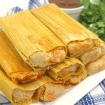 pork tamales stacked on a white serving plate