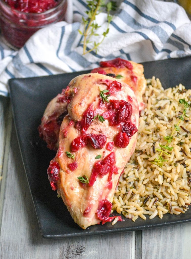 two pieces of cranberry orange chicken served on a black square plate with long grain & wild rice on the side