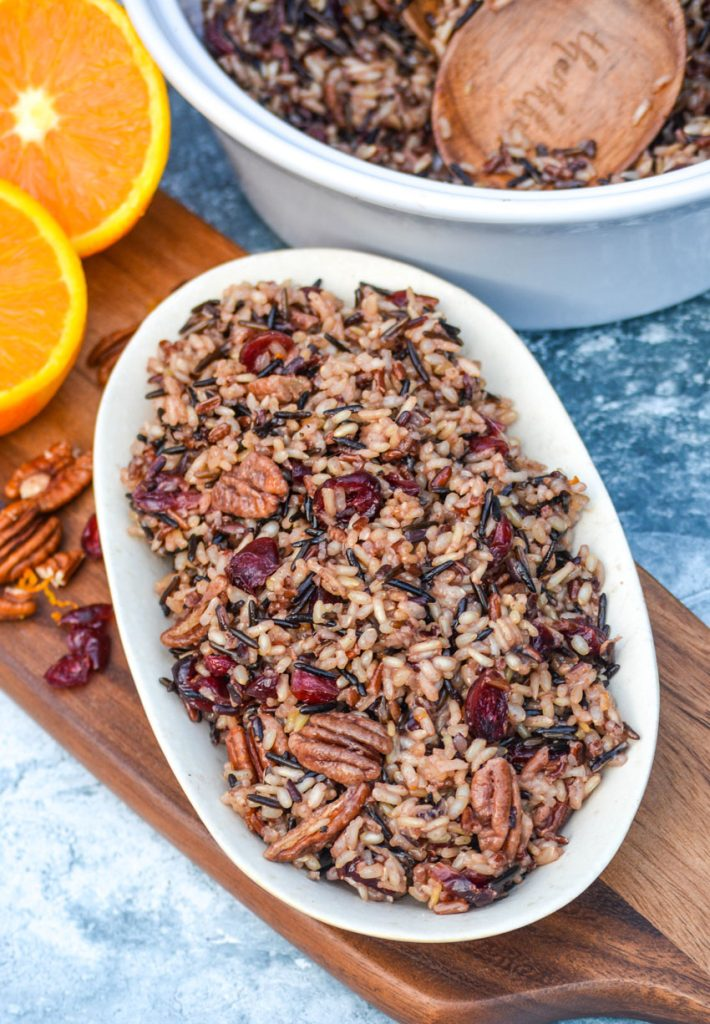 cranberry pecan wild rice stuffing shown on a small white platter on a wooden cutting board with fresh fruit and nuts