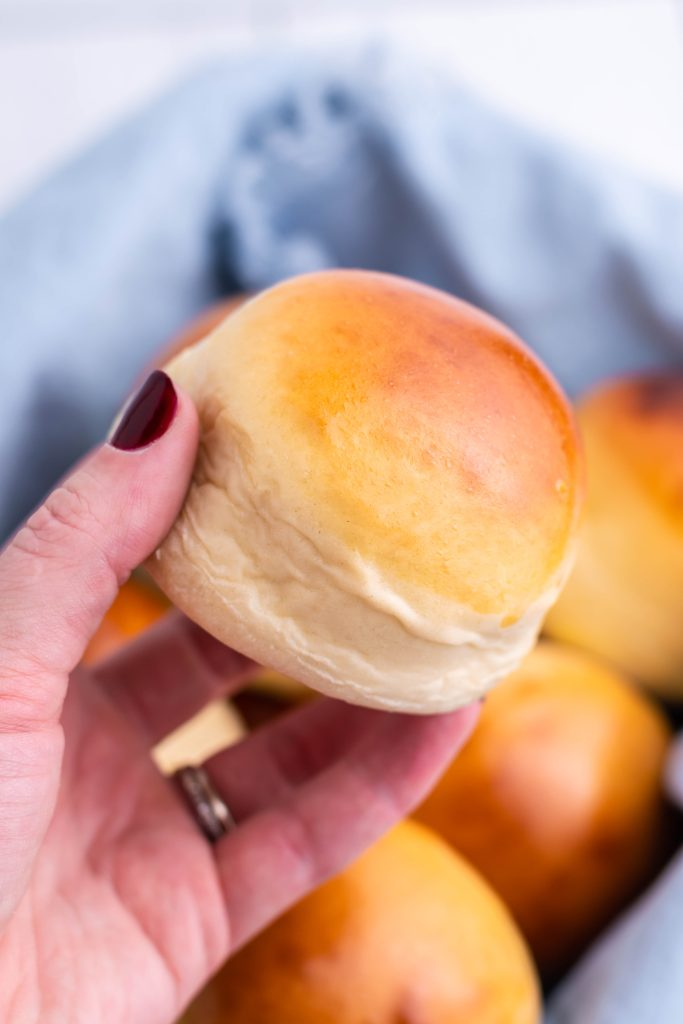 a hand holding up a freshly baked homemade hamburger bun