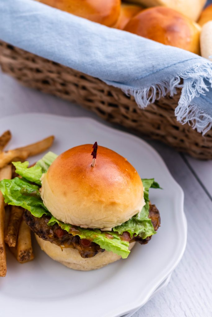 a fully loaded burger using homemade hamburger buns shown on a white plate with a side of fries and bread basket in the background