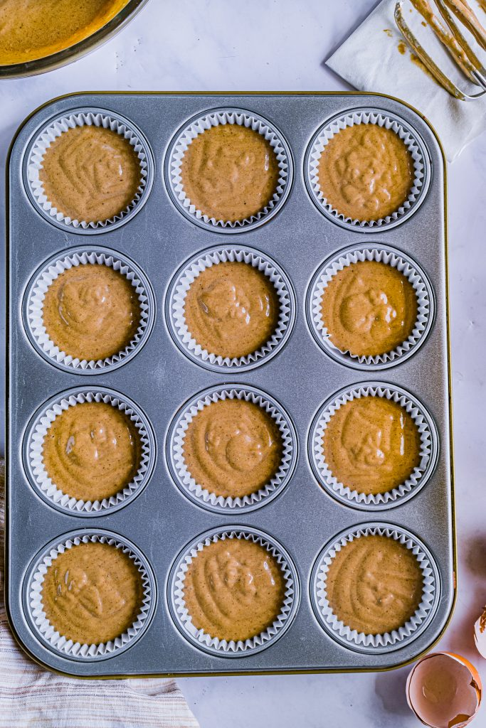 gingerbread cupcake batter shown poured into white paper lined muffin tins
