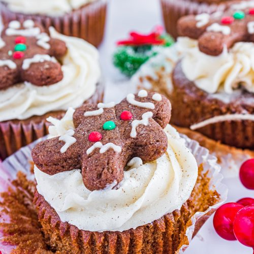 gingerbread cupcakes with spiced butter cream are shown topped with frosted gingerbread cookies