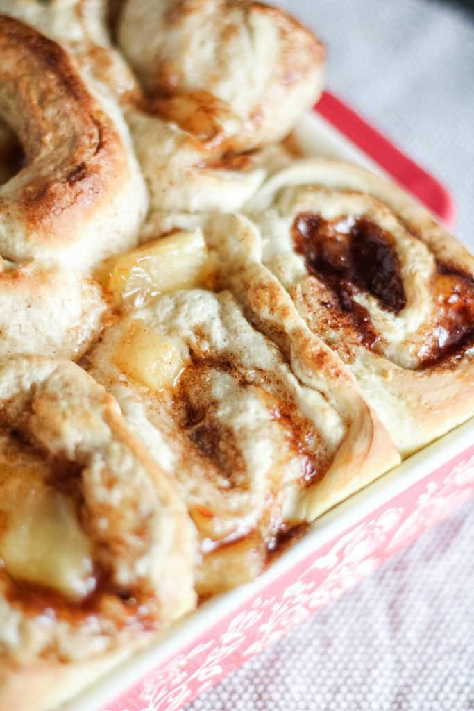 caramel apple cinnamon rolls shown baked in a red square baking dish