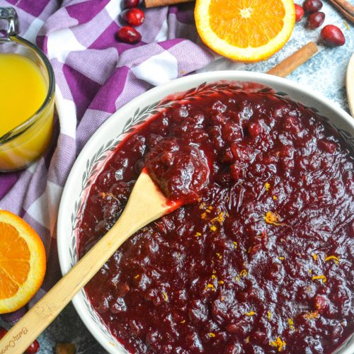Instant pot cranberry sauce shown in a large shallow white serving dish with a wooden spoon for serving