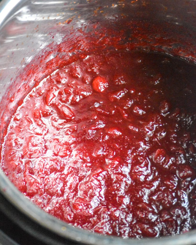 Instant Pot cranberry sauce shown in the liner of the Instant Pot pressure cooker after cooking down