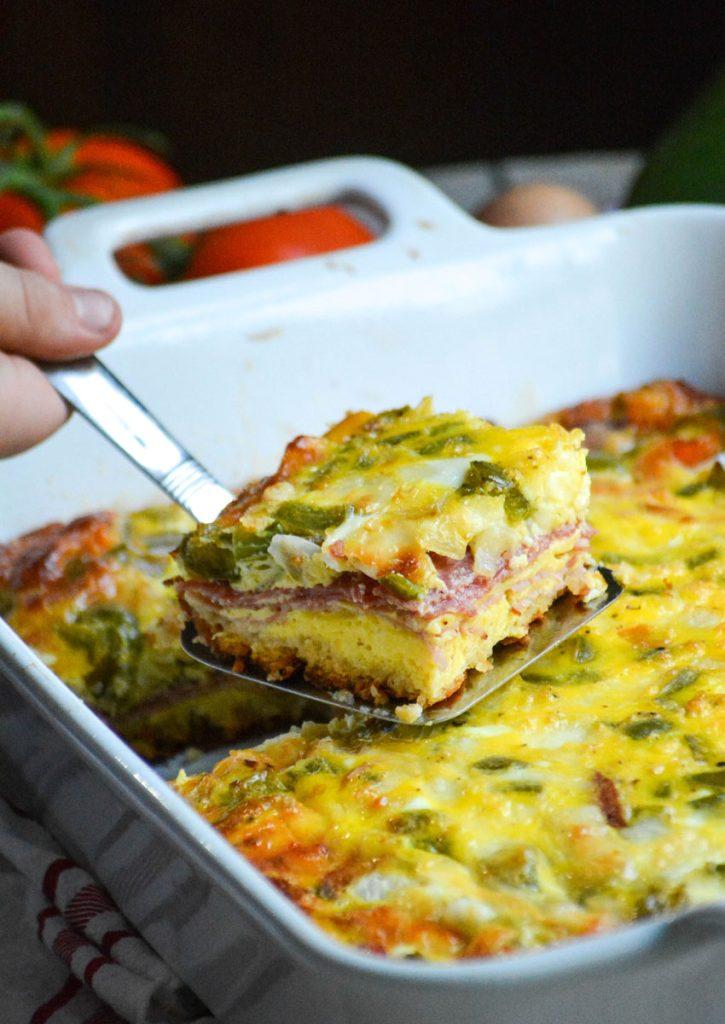 a silver spatula holding up a freshly cut slice of Italian breakfast bake style casserole