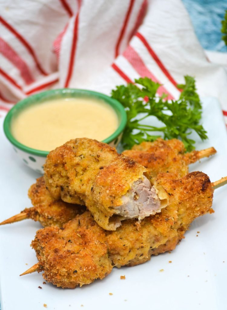 three skewers of Nonna's fried city chicken on a white platter served with fresh herbs and honey mustard sauce for dipping