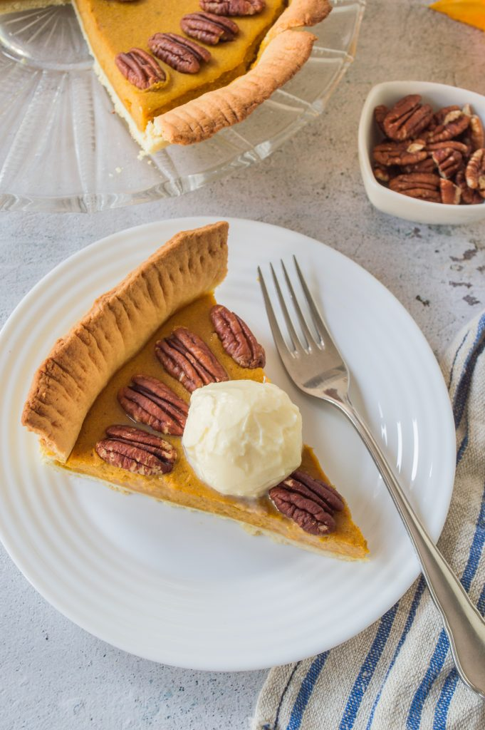 a slice of homemade pumpkin pie with pecans served on a small white plate with silver forks for eating
