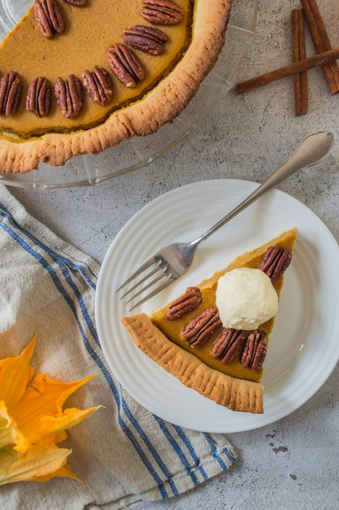 a slice of pumpkin pie with pecans served on a small white plate with silver forks for eating
