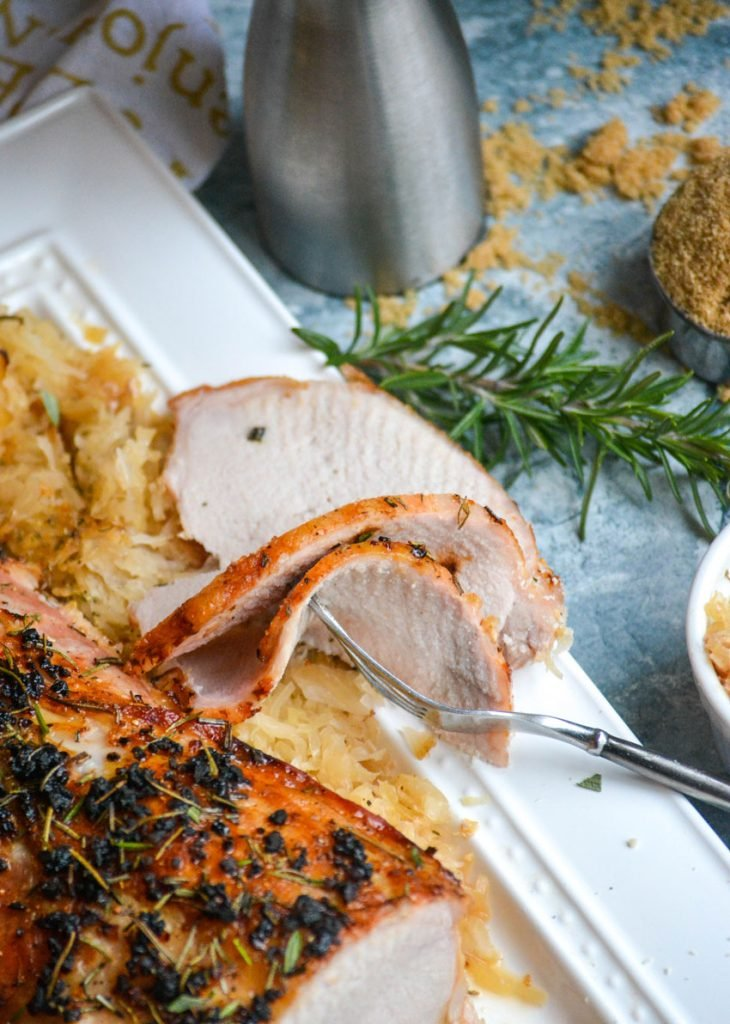 roasted pork loin with rosemary brown sugar sauerkraut shown on a white platter, surrounded by the sweetened cabbage and thinly sliced